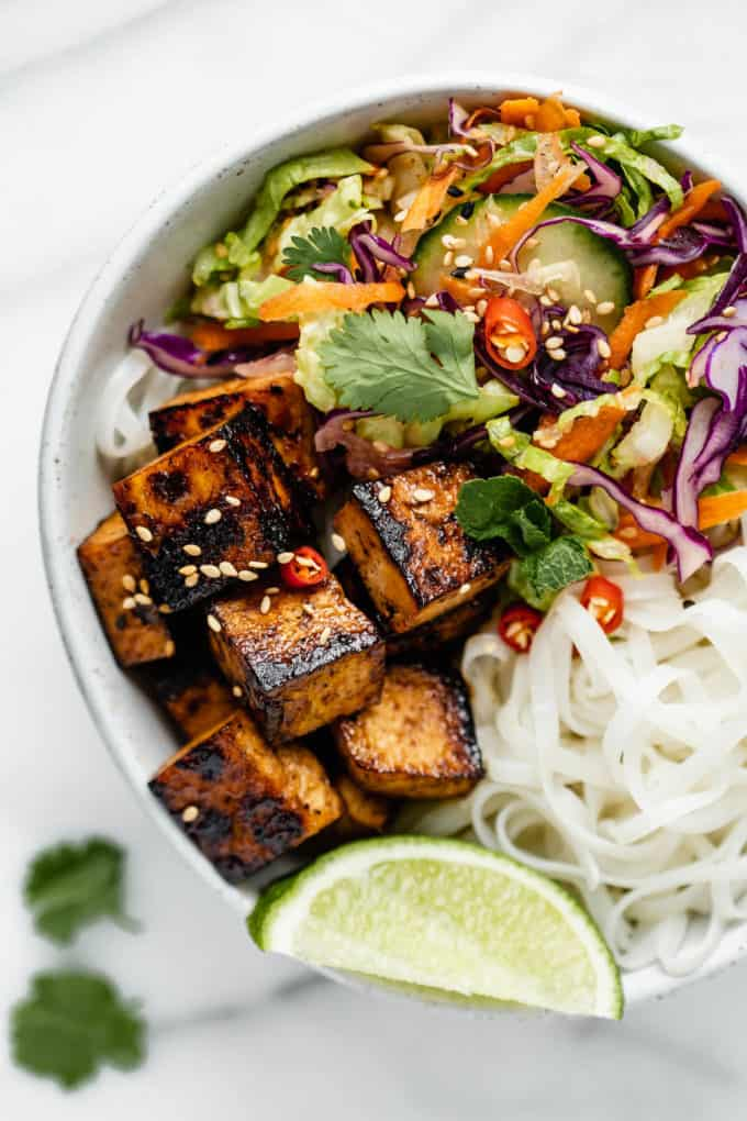 A bowl with tofu, salad and rice noodles in it