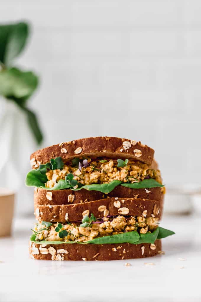 two chickpea salad sandwiches stacked on a marble counter
