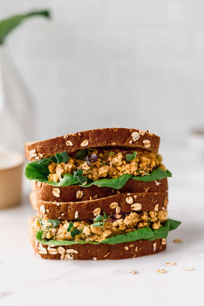 two smashed chickpea salad sandwiches stacked on top of each other