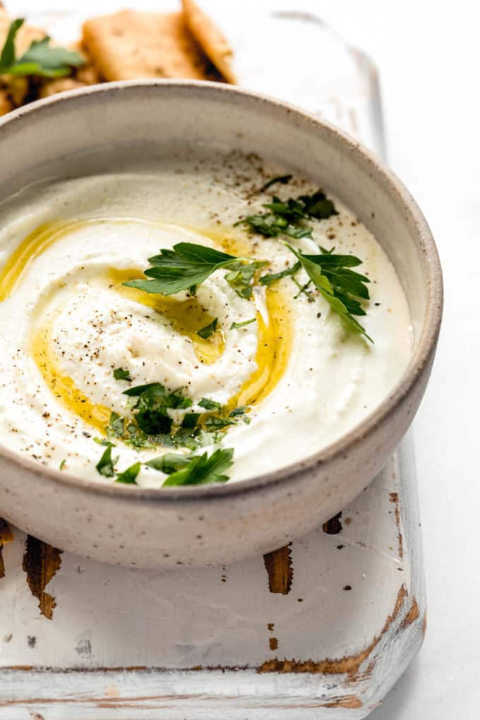 A bowl of whipped feta dip with olive oil and parsley on top