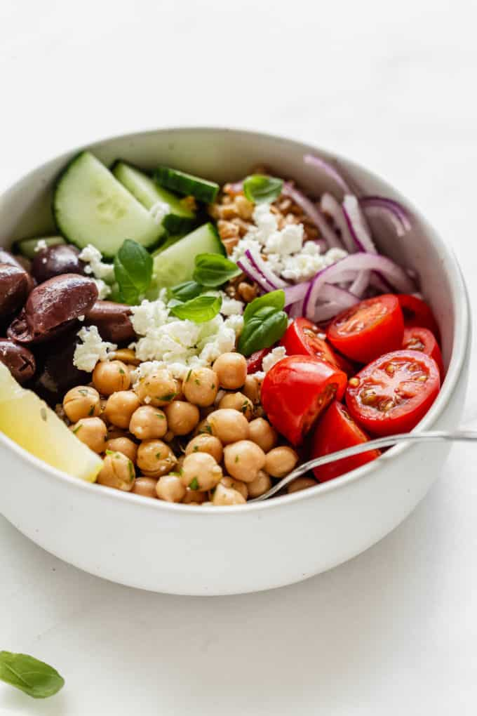 A greek power bowl with chickpeas and vegetables in a white bowl