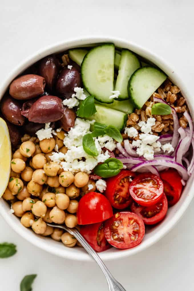 chickpeas, vegetables, and olives in a white bowl