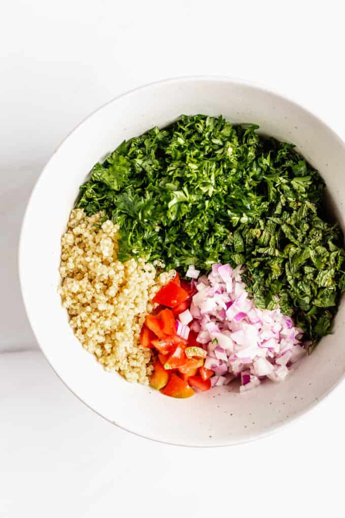 Parsley, mint, red onion, red pepper and quinoa in a mixing bowl
