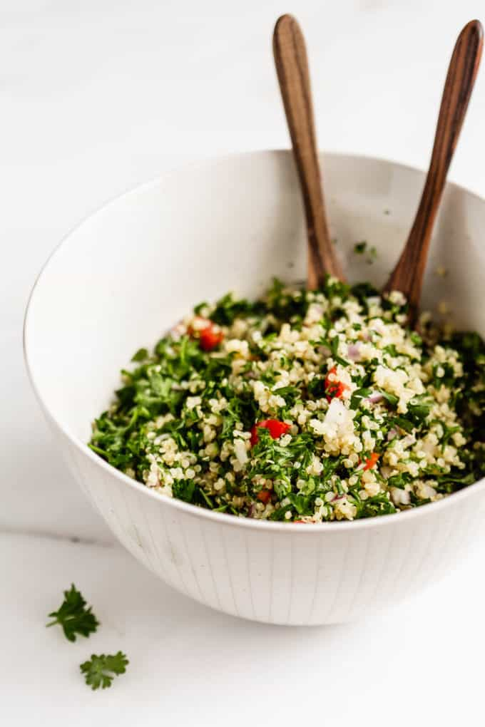 A bowl of quinoa tabbouleh salad with wood serving spoons