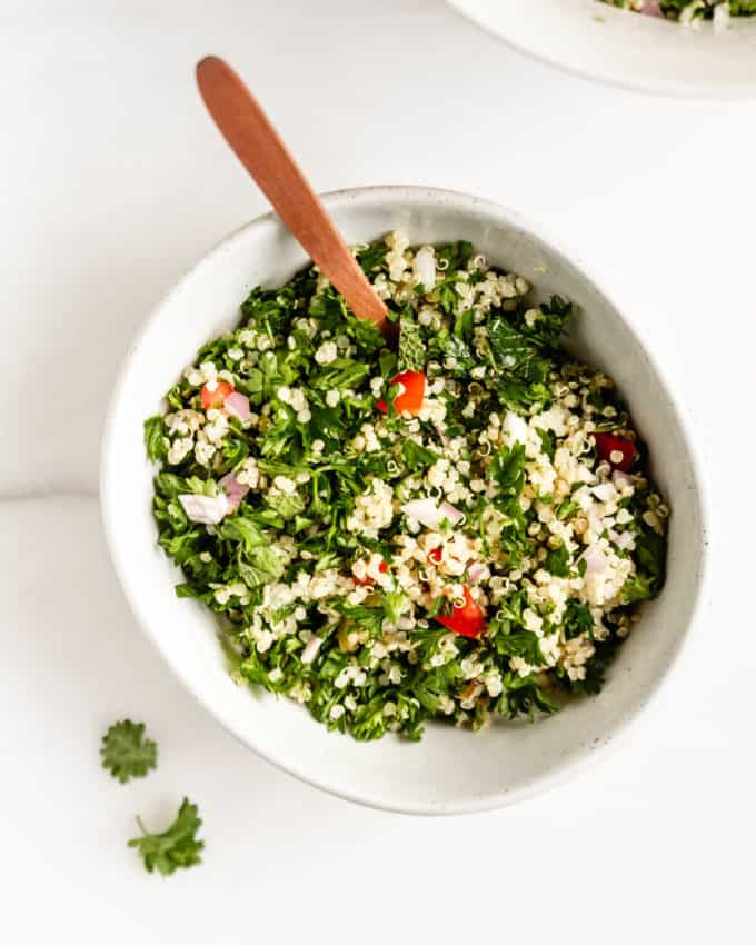 Quinoa tabbouleh salad in a white bowl with a wood spoon