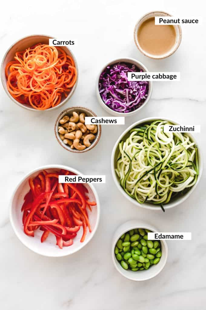 A flat lay of carrots, zucchini, peppers, cabbage, edamame, cashews and peanut sauce in bowls