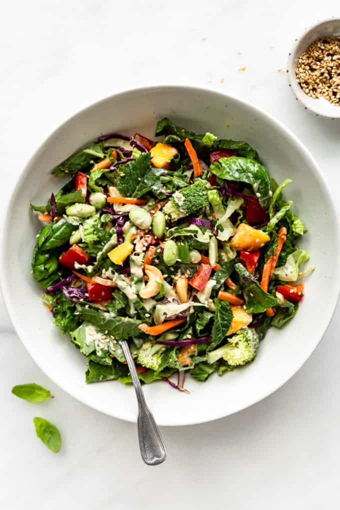 A Thai Crunch Salad with Sesame dressing in a white bowl with a fork in it