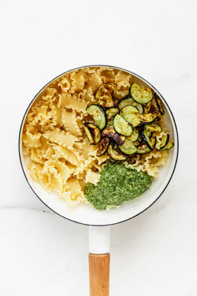 Noodles, roasted zucchini and pesto in a white pot