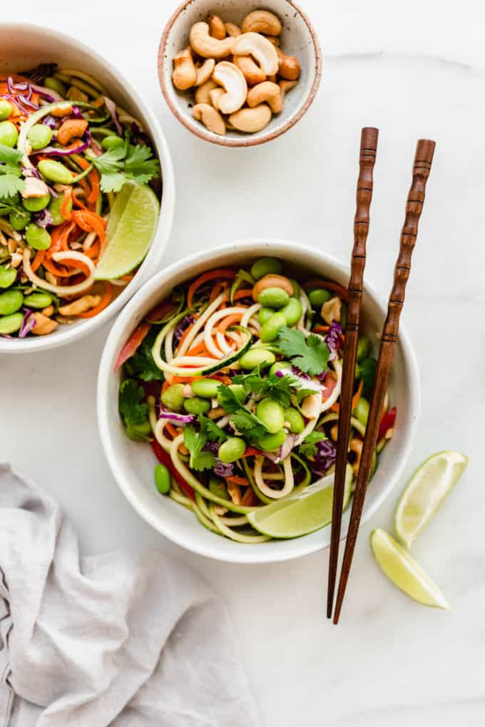 Two bowls of raw pad Thai made of spiralized zucchini topped with edamame