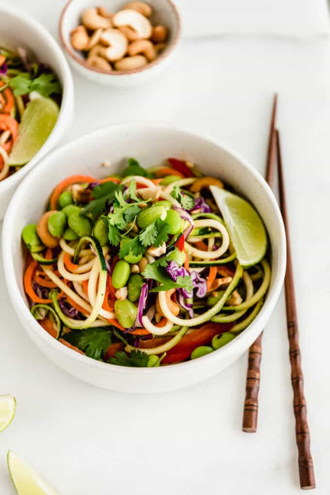 A bowl of spiralized zucchini and carrots topped with edamame and cilantro