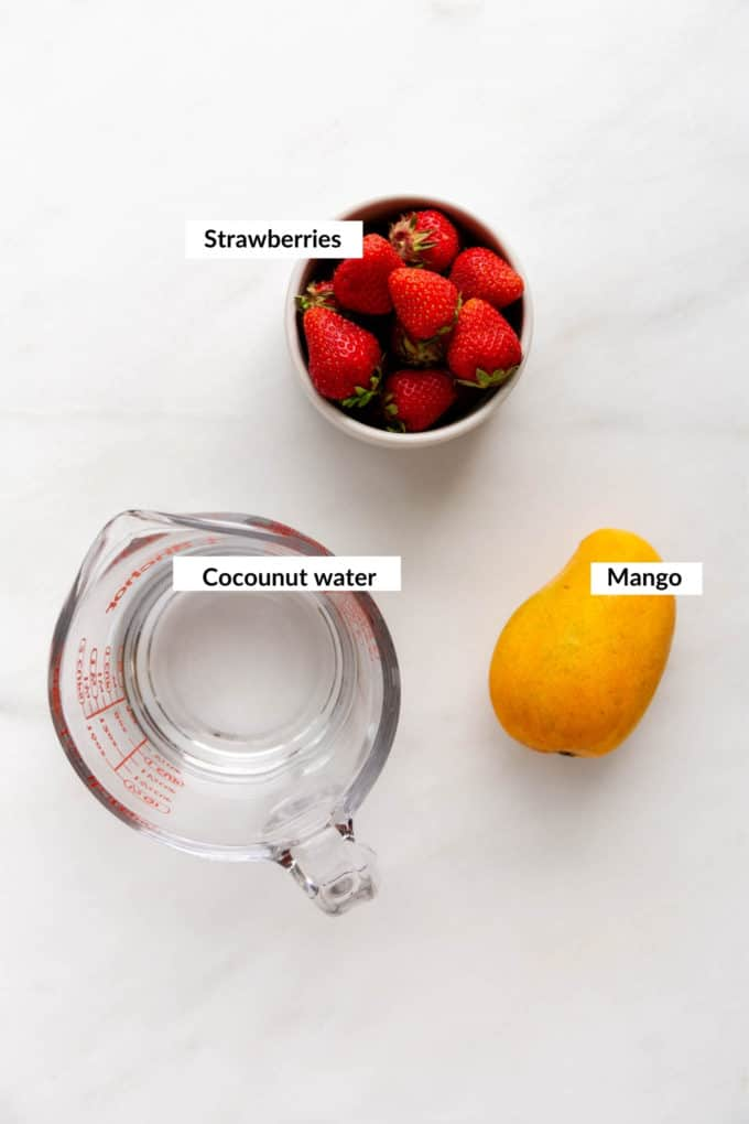 a mango, bowl of strawberries and measuring cup on a marble table