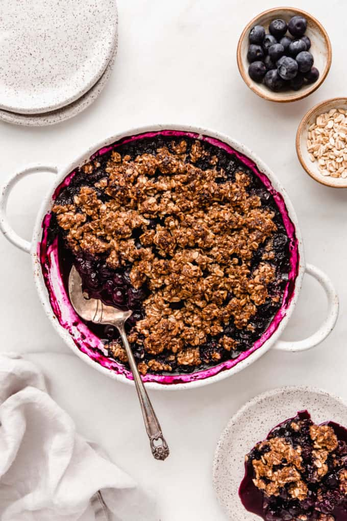 A blueberry crisp dishes and a napkin on the side