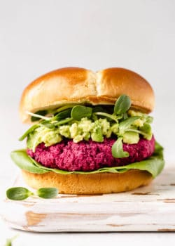 A vegan beet burger in a bun with avocado, sprouts and lettuce