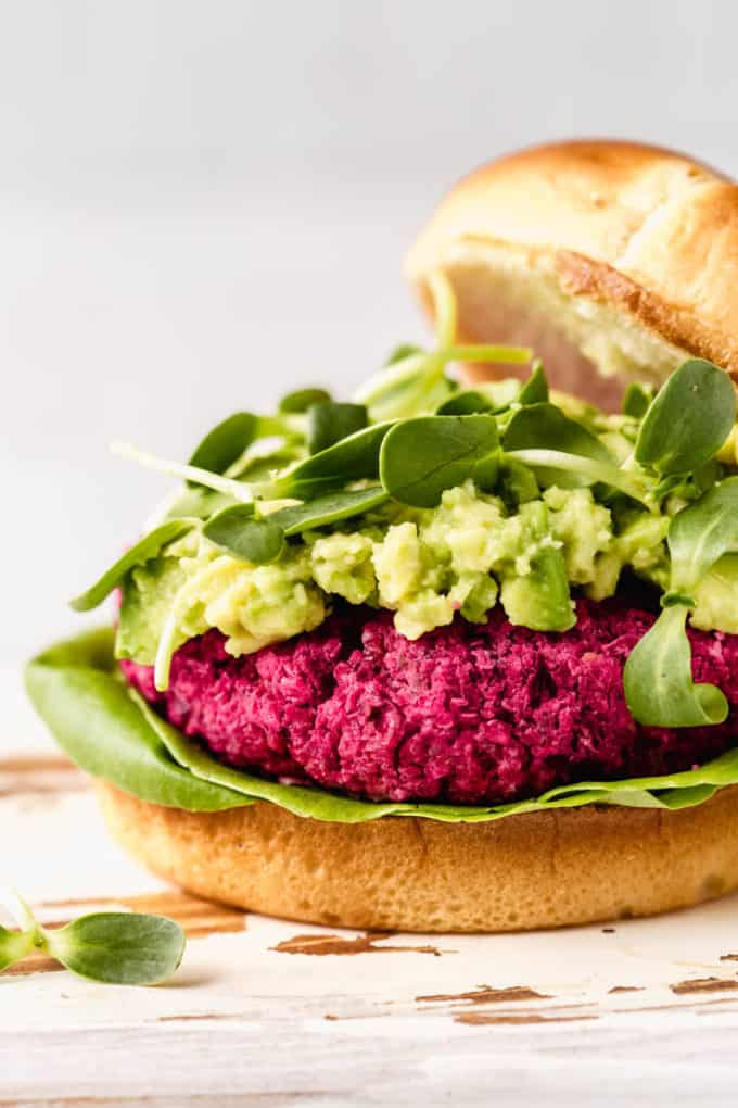 A close up of a vegan beet burger topped with mashed avocado and sprouts