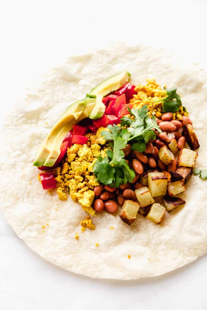 A tortilla with potatoes, beans, tofu, peppers and avocado on it