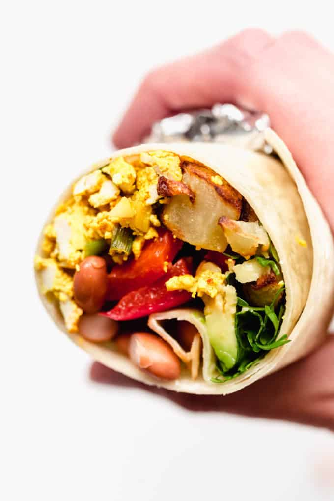 A hand holding a half of a vegan breakfast burrito
