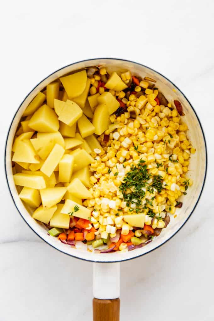a white pot with potatoes, corn and thyme in it
