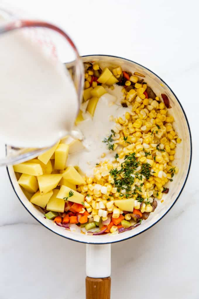 a measuring cup pouring cashew cream into a pot of vegetables