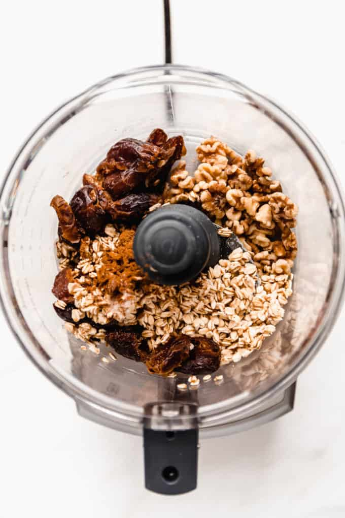 A food processor with dates, walnuts and oats in it