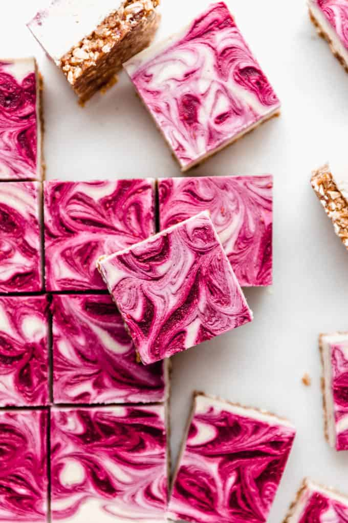 Vegan raspberry cheesecake bars cut into squares on a marble board