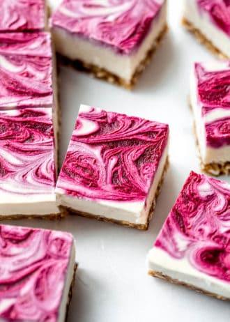 Vegan raspberry cheesecake bars with raspberry swirl on top on them