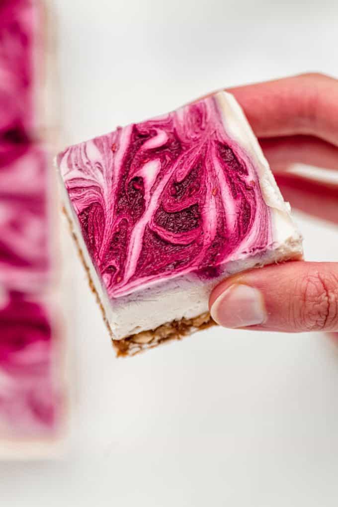 A hand holding a vegan raspberry cheesecake bar