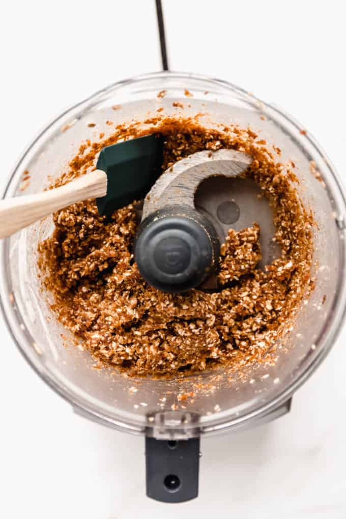 A food processor with blended date, walnuts and oats in it