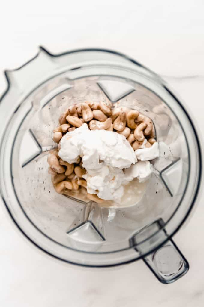 A blender with cashews and coconut cream in it