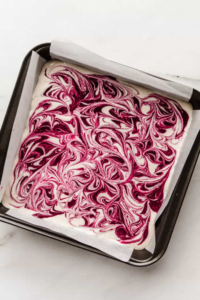 A baking pan with swirled vegan raspberry cheesecake in it