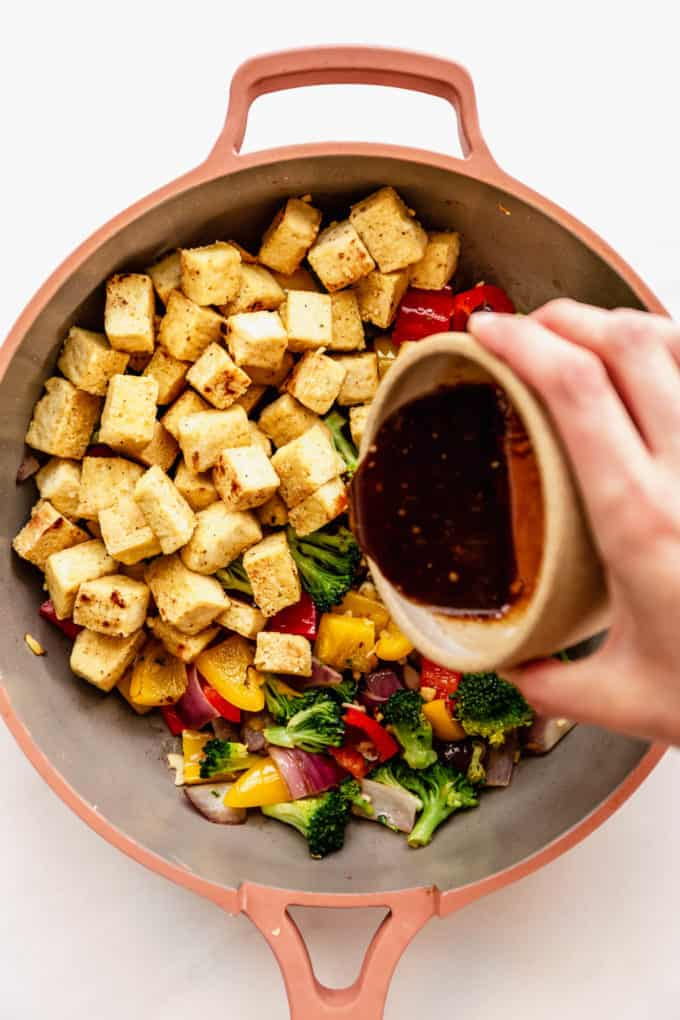 a hand pouring stir fry sauce into a pan of tofu and vegetables