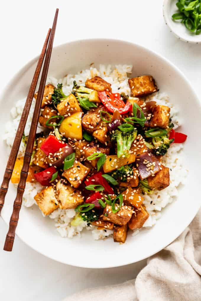 a bowl of tofu stir fry with veggies served over rice