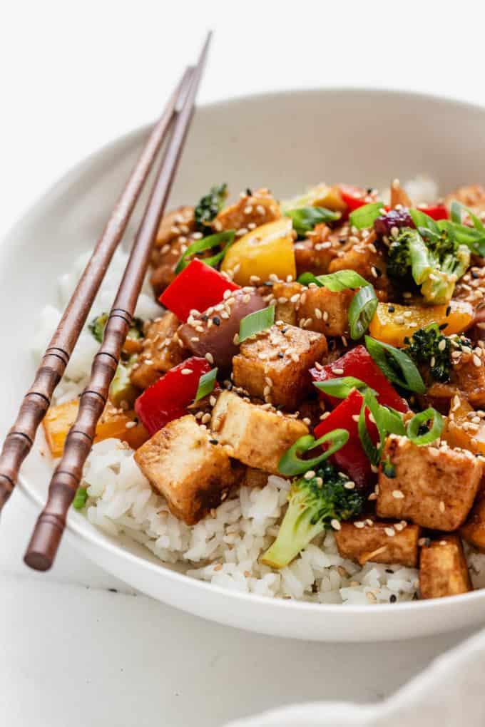 Tofu stir fry in a white bowl with wood chopsticks