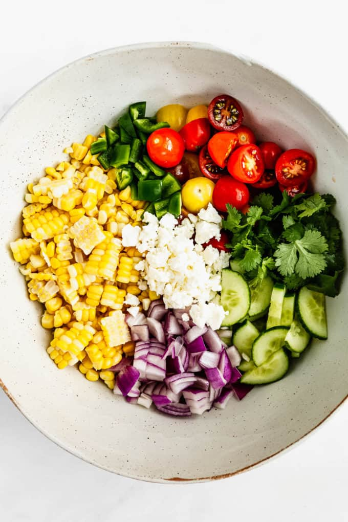A bowl with corn, tomatoes, onion, cucumber, herbs and feta in it