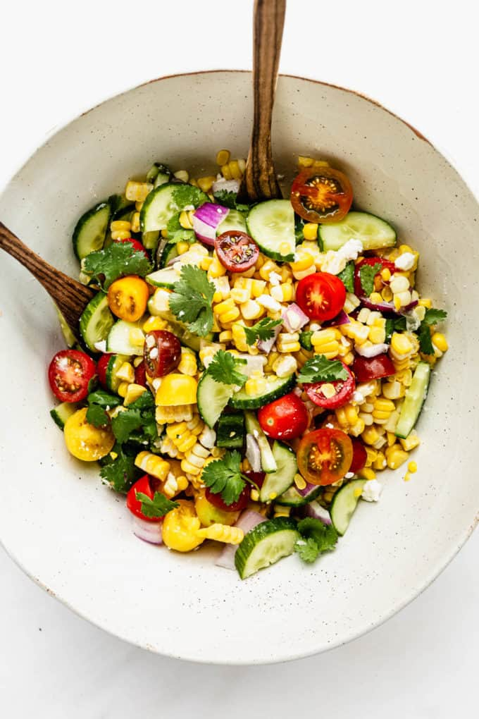 Summer corn salad in a large mixing bowl with wood spoons