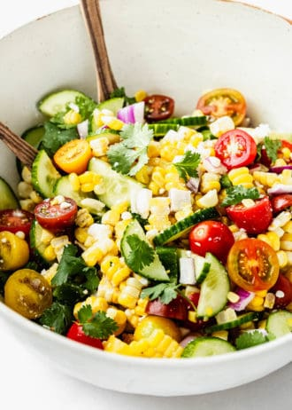 A salad with corn, cucumber and tomato in it