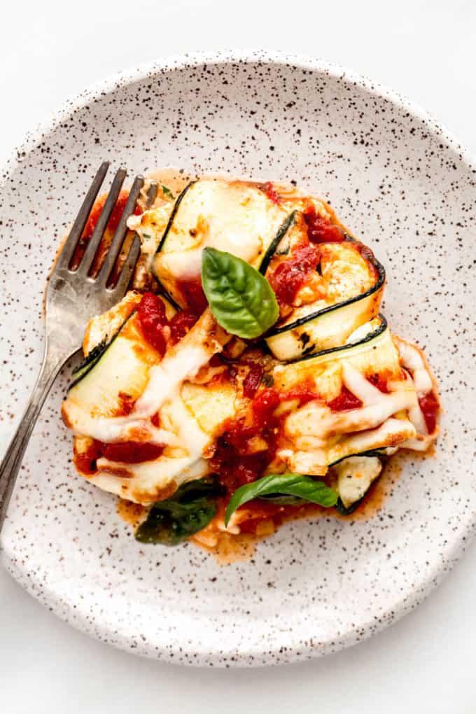 Zucchini involtini on a white speckled plate