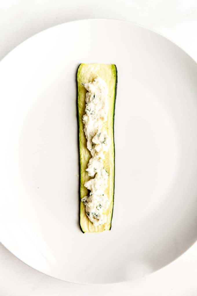 A slice of zucchini with ricotta spread in the centre