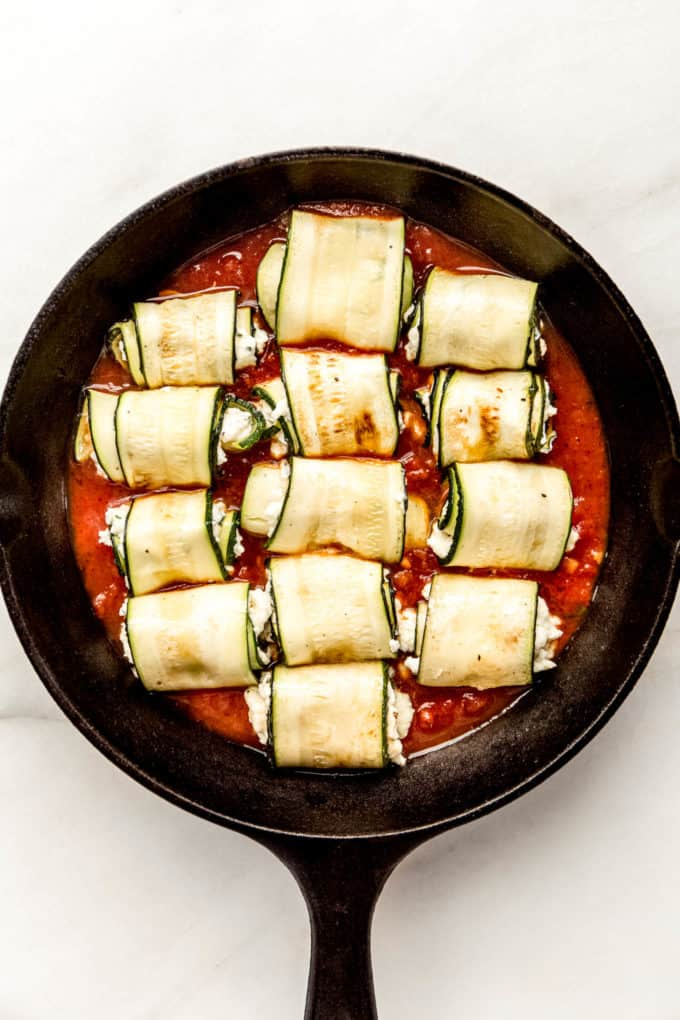 zucchini roll ups on tomato sauce in a cast iron skillet