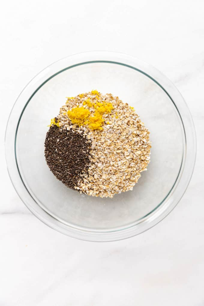 A clear mixing bowl with oats, chia seeds and lemon zest
