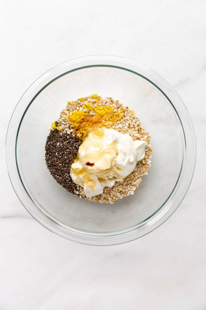 A mixing bowl with oats, lemon zest, chia seeds, yogurt and honey in it