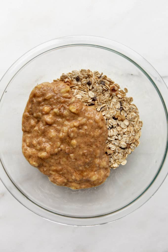 oats in a mixing bowl with mashed banana and almond butter