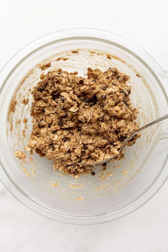 mixed up oats, chocolate chips, banana and almond butter in a clear mixing bowl