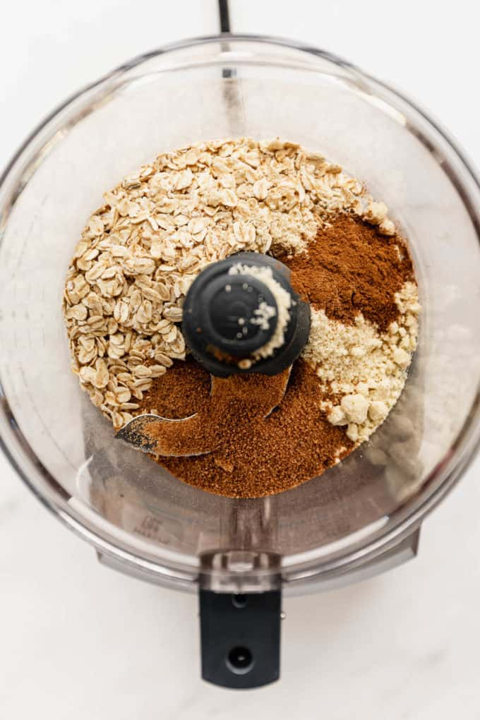 A food processor with oats, coconut sugar and almond flour in it