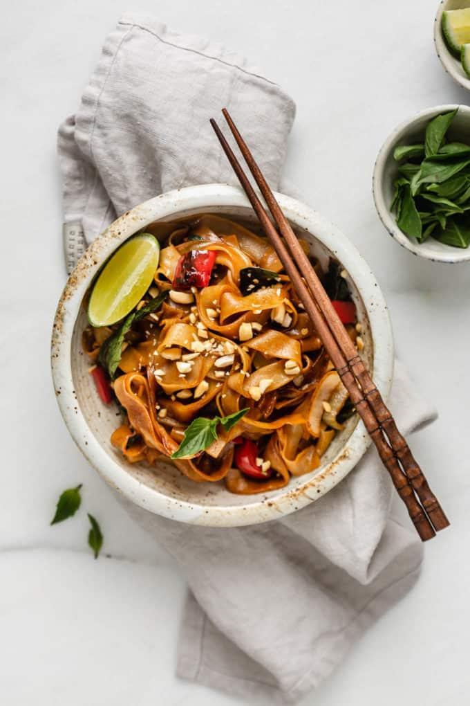 Thai drunken noodles in a bowl on a grey napkin with chopsticks