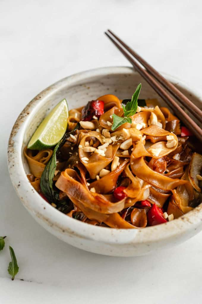 A bowl of Thai drunken noodles topped with crushed peanuts and a lime wedge