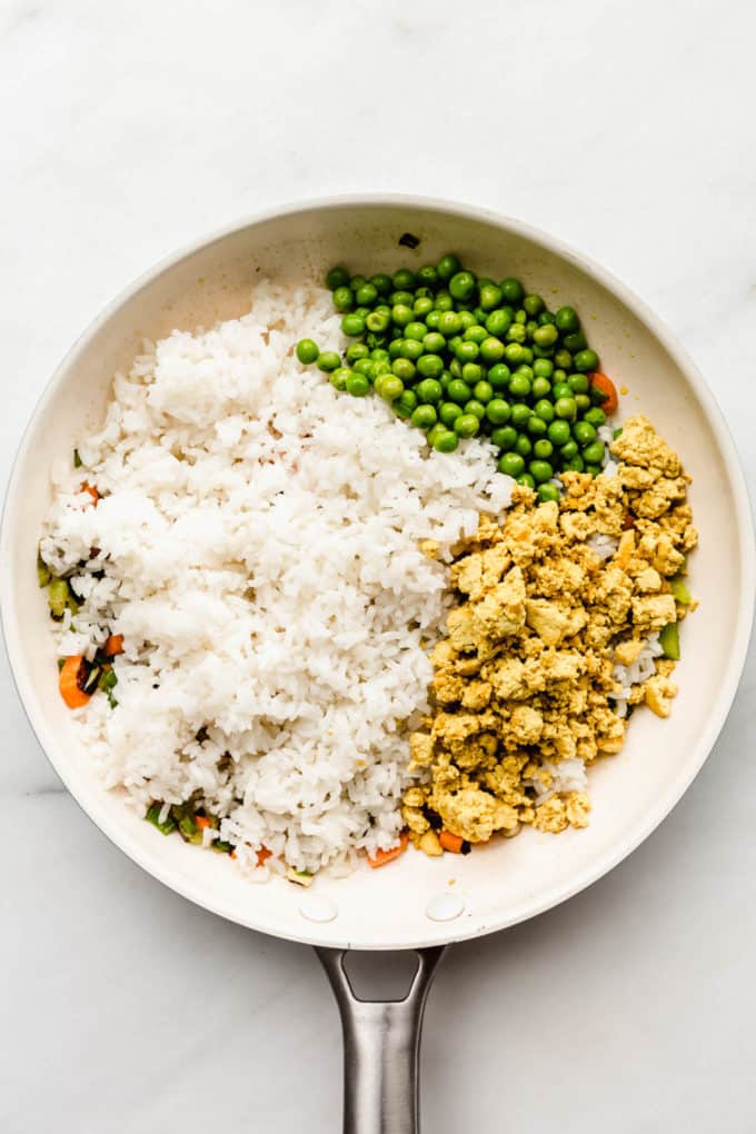 A white pan with rice, scrambled tofu and peas in it