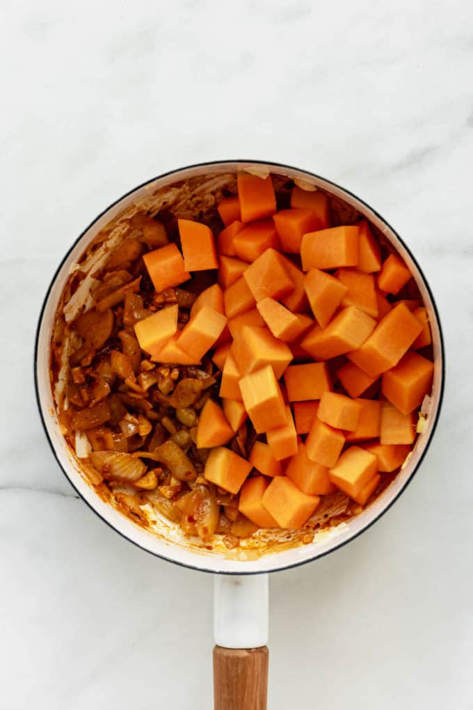 A white pot with cubed butternut squash and onions in it
