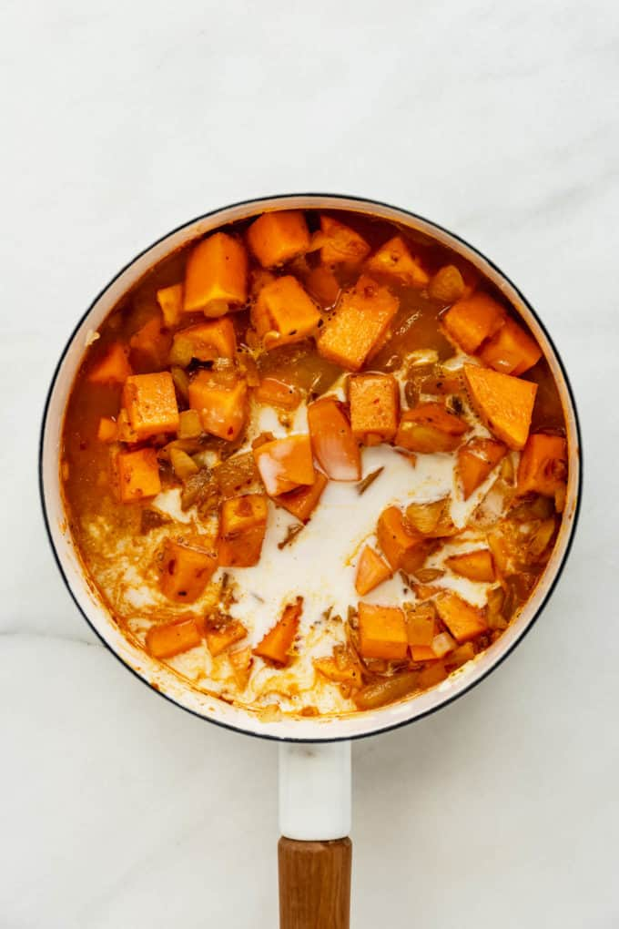 A white pot with squash, broth and coconut milk in it