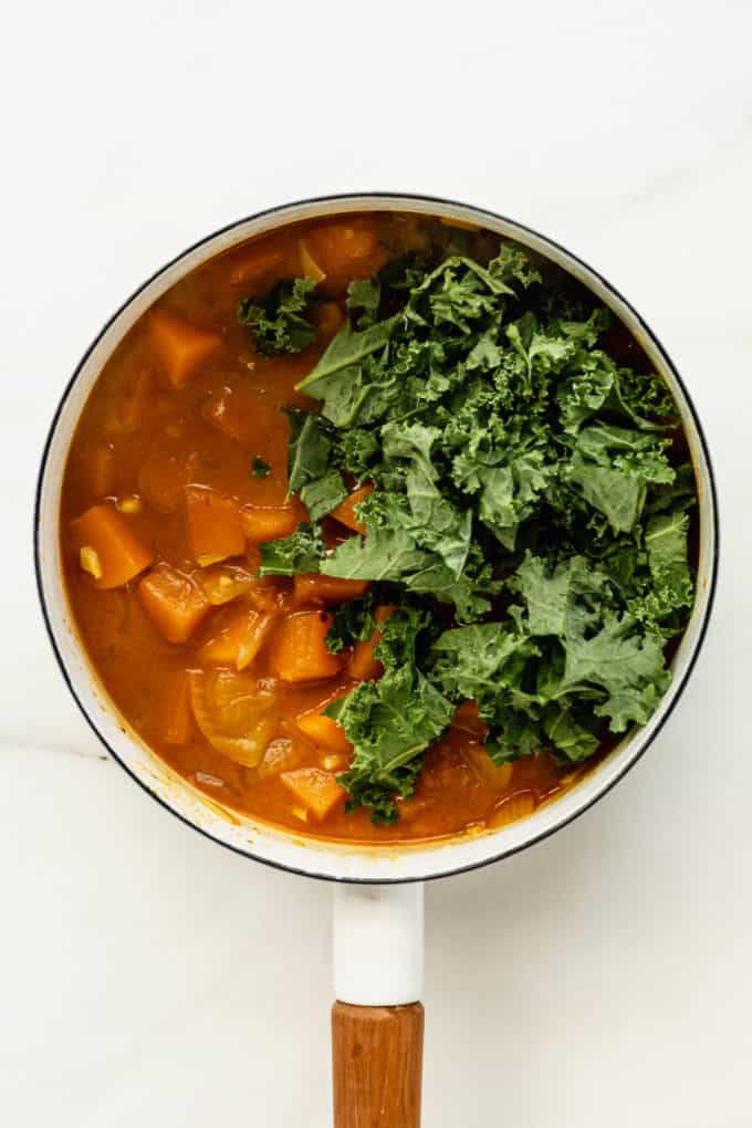 A white pot with squash curry and fresh kale leaves in it