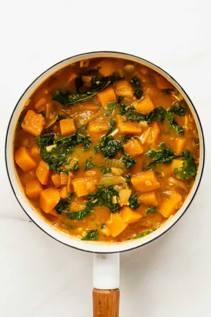 a white pot with butternut squash and kale curry in it